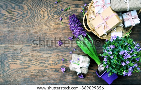 spring flowers and gifts, wooden background with space for text, rustic lifestyle - stock photo