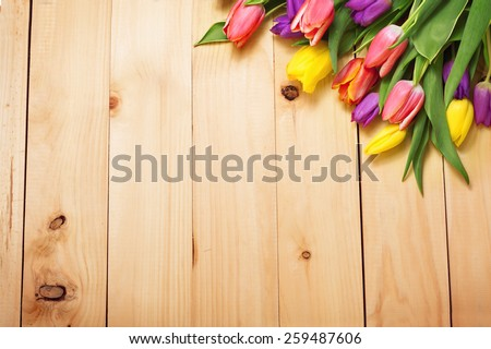 Spring Flowers bunch at wood floor texture. Beautiful Tulips bouquet gift. Easter or Mother's Day  background. Springtime or summertime. Invitation card design with space for your text - stock photo