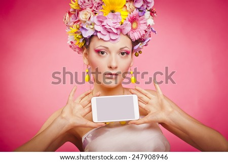 Spring flowers girl is holding smartphone in hands - stock photo