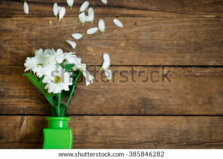 spring flowers in a green vase on a wooden background - stock photo