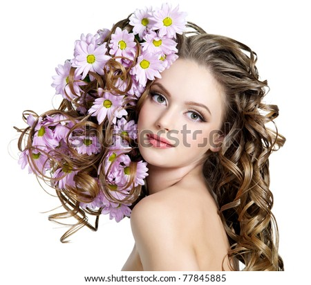 Spring flowers in beautiful long hair of young woman - white background