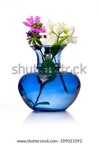 Spring flowers in blue vase isolated on white background - stock photo