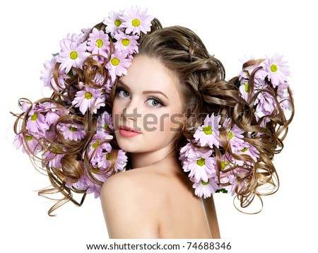 Spring flowers in gorgeous long curly hair of young beautiful woman - white background - stock photo