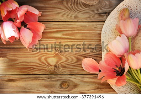 Spring flowers tulips with a straw sun hat  - stock photo