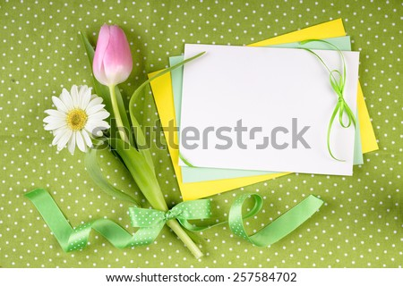 Spring frame for your greeting card with flowers and ribbons in green, yellow and pink - stock photo