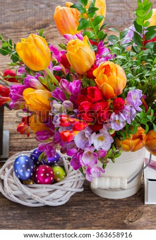 Spring fresh  flowers with easter eggs in nest