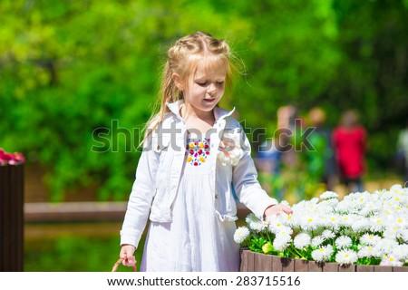 Spring garden, spring flowers, dorable little girl and tulips - stock photo