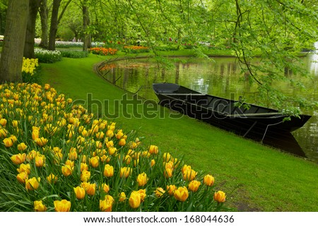 spring garden with canal and boat,   'Keukenhof', Holland - stock photo