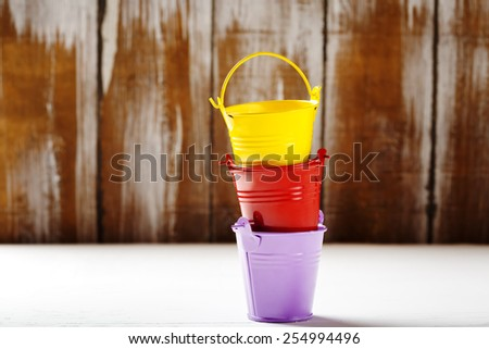 Spring gardening background with cute little colorful garden buckets - stock photo