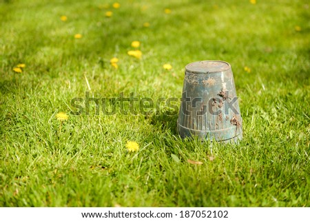 Spring gardening - overturned pot upside down in grass, copyspace - stock photo