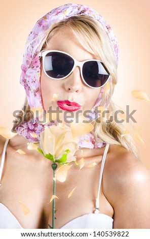 Spring girl blowing on a peach rose with enchanting style when enjoying the natural beauty in nature - stock photo
