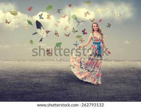 Spring girl in a long dress color walks outdoors, and her flying butterflies and birds. - stock photo