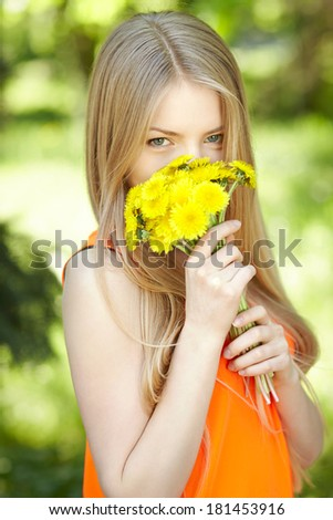 Spring girl. Lovely blond girl smelling bunch of dandelions outdoors. - stock photo