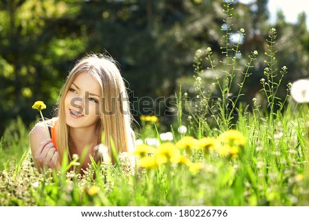 Spring girl lying on the field of dandelions - stock photo