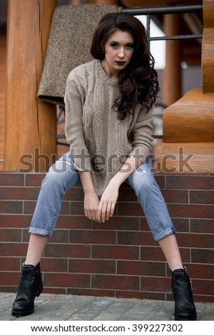 Spring in the country style. Full length portrait of young woman in white knitted sweater and furry hat standing in the front of rustic wood wall in the yard near house, wearing sweater