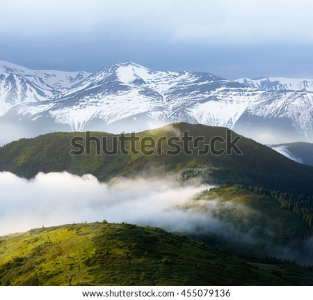 Spring in the mountains. Evening landscape with fog and snow covered peaks. Collage of two frames - stock photo