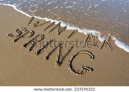 Spring is coming concept - inscription Winter and Spring written on a sandy beach, the wave is starting to cover the word Winter. - stock photo