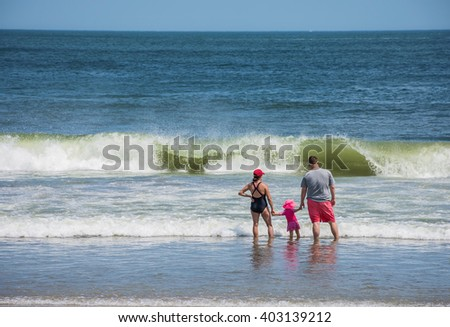 SPRING LAKE, NEW JERSEY-AUGUST 1 - Parents hold their daughters hand in the surf on August 1 2015 in Spring Lake New Jersey. - stock photo
