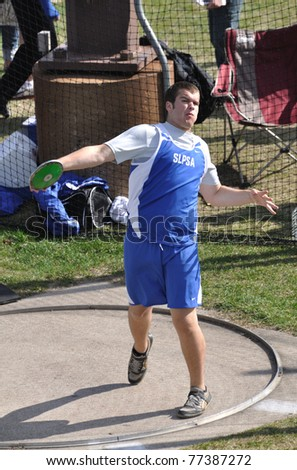 SPRING LAKE PARK, MN - May 3: Unidentified Teen Boy Throwing the Discus at a High School Track and Field Meet on May 3, 2011 in Spring Lake Park, Minnesota. - stock photo
