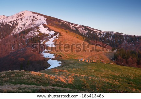 Spring landscape in the mountains. Evening light of the setting sun. Last snow on the mountain slopes. Carpathians, Ukraine, Europe - stock photo