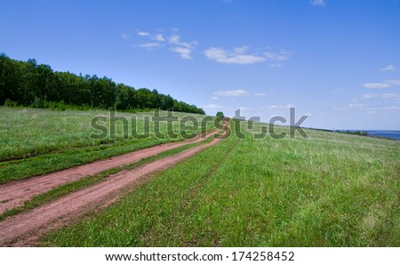 spring landscape of rural dirt road leading to the horizon through a meadow near the forest on a sunny day