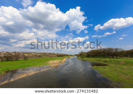 Spring landscape on river under nice clouds in sky - stock photo