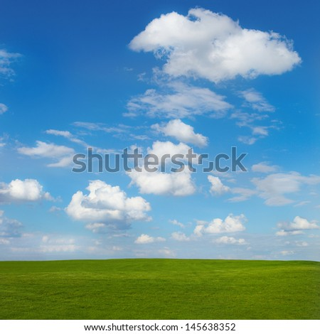 Spring landscape with green field and blue sky - stock photo
