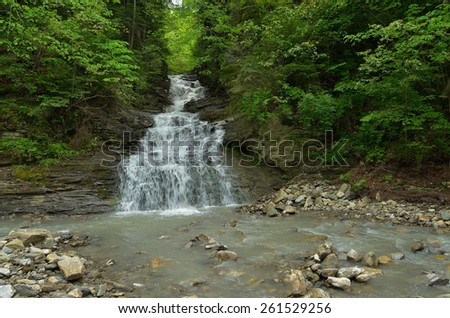 Spring landscape with mountain waterfall - stock photo