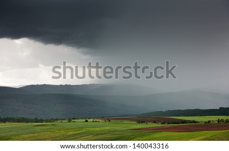 Spring landscape with rain over mountains and green field - stock photo