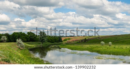 Spring landscape with river, wood and hill, beautiful sky - stock photo