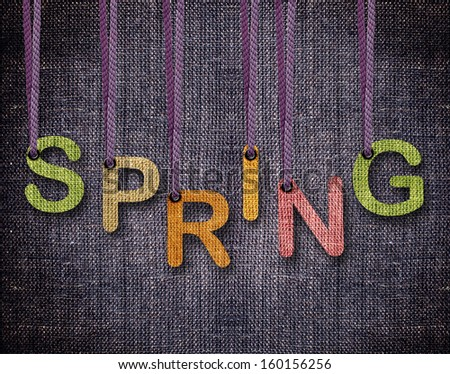 Spring letters hanging strings with blue sackcloth background. - stock photo