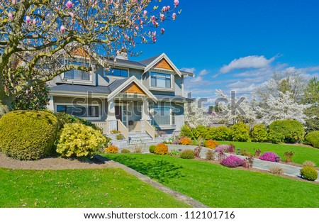 Spring memory, sherry blossom time. Big custom built luxury  home in the suburbs of Vancouver, Canada - stock photo