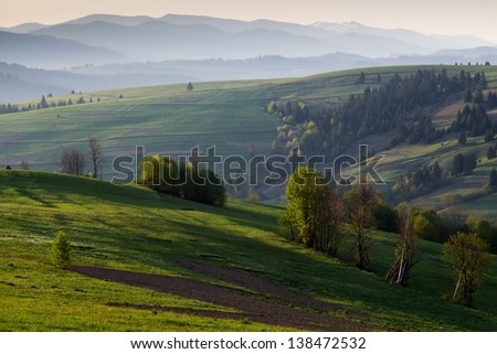 Spring morning rural landscape in the Carpathian mountains. The sun's rays illuminate the colorful hills