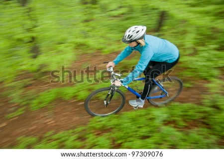 Spring mountain biking down the trail - stock photo