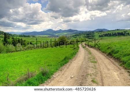 Spring mountain landscape. Mountain trail and forested hills.