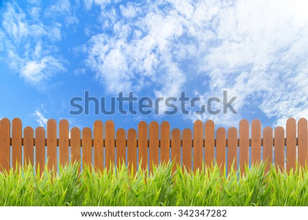 Spring or summer nature background with grass field and wooden fence - stock photo