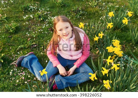 Spring portrait of a cute little girl of 8-9 years old, having fun outdoors, playing with flowers - stock photo