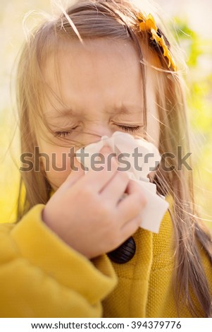 spring portrait of a little girl is blowing her nose - stock photo