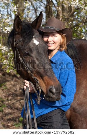 Spring portrait of cowgirl with her horse at flowering trees