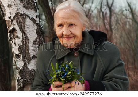 Spring portrait of the smiling elderly woman, in a forest with spring flowers - stock photo