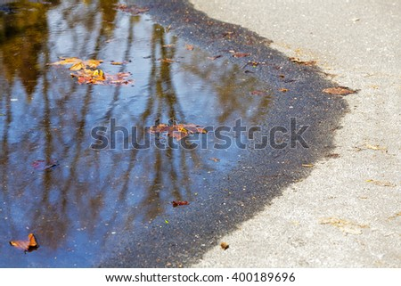 Spring puddle on the path in which drowned still autumn leaf - stock photo