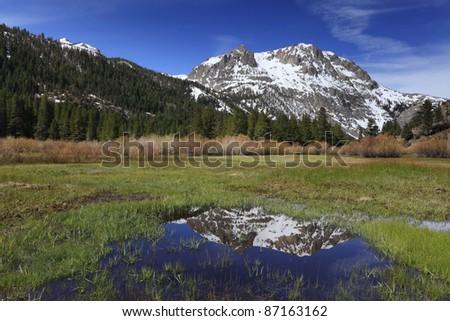 Spring reflections of Carson Peak near June Lake in eastern Sierra Nevada mountains of California - stock photo