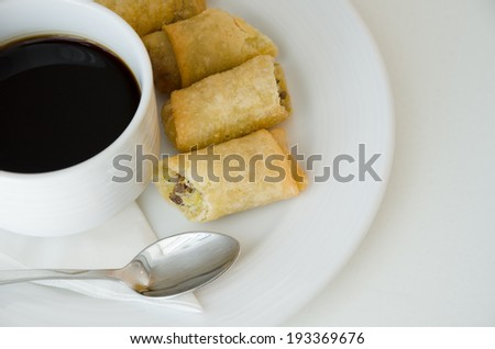 Spring roll or egg roll and cup of coffee.