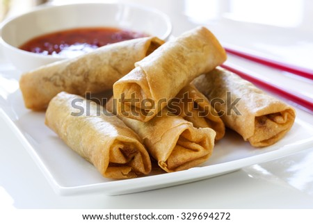 Spring rolls with chili sauce and chopsticks.   - stock photo