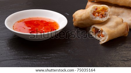 Spring rolls with sweet chili dipping sauce on dark grey slate background. - stock photo