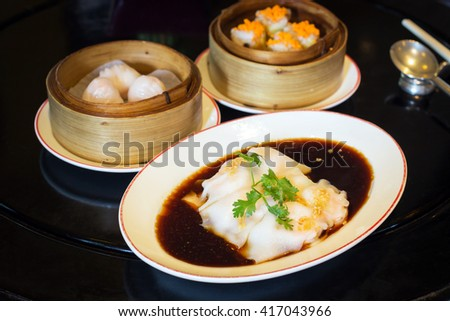 Spring rolls with sweet sauce and dumplings on the table - stock photo