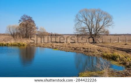 Spring rural landscape with a lake and fence