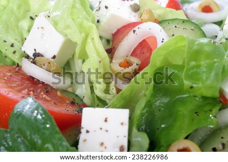 Spring salad, Colorful vegetable salad. Salad with lettuce, tomato, cucumber, onion, olives clearing sauce. - stock photo