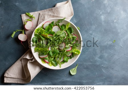 Spring salad with radishes on dark background, selective focus
