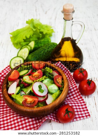 Spring salad with tomato, cucumbers and radish on a wooden background - stock photo